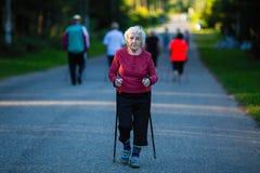 Femme agée occupée dans le nordic marchant avec des bâtons sport image stock