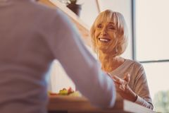 Femme agée optimiste parlant avec l'ami tout en mangeant  Photos stock
