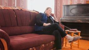 Femme agée parlant au téléphone dans l'appartement Photos libres de droits