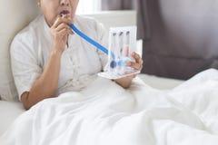 Femme agée patiente employant l'incentivespirometer ou trois boules pour pour stimuler le poumon dans la chambre photos stock