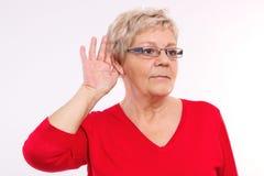 Femme agée plaçant la main sur l'oreille, difficulté dans l'audition dans la vieillesse photographie stock