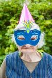 Femme agée portant la célébration colorée de masque et de chapeau Photos libres de droits