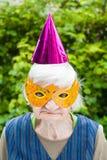 Femme agée portant la célébration colorée de masque et de chapeau Images libres de droits