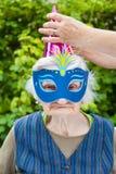 Femme agée portant la célébration colorée de masque et de chapeau Photographie stock