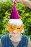 Femme agée portant la célébration colorée de masque et de chapeau Photos stock