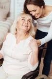 Femme agée positive s'asseyant dans le fauteuil roulant Photo stock