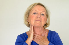 Femme agée réfléchie avec sa main à son cou Photographie stock