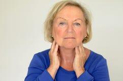 Femme agée réfléchie avec ses mains à son cou Photographie stock libre de droits