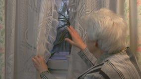 Femme agée regardant à la fenêtre banque de vidéos