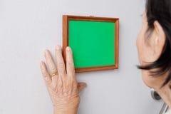 Femme agée regardant une photo de souvenirs sur le mur Image stock