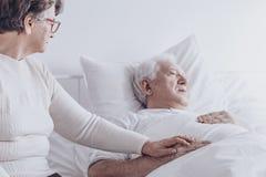 Femme agée rendant visite au mari malade Photos stock