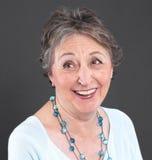 Femme agée riant - une femme plus âgée d'isolement sur le backgroun noir Images stock