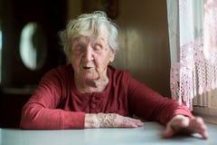 Femme agée russe parlant avec émotion se reposer à une table Image stock