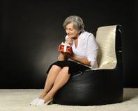 Femme agée s'asseyant avec le cadeau Image stock