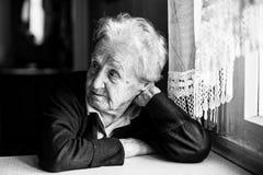 Femme agée s'asseyant dans la cuisine près de la fenêtre Photo libre de droits