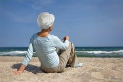 Femme agée s'asseyant dans le sable sur la mer de plage Image stock