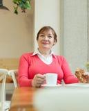 Femme agée s'asseyant en café Photos stock