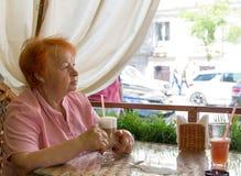 Femme agée s'asseyant en café pendant l'après-midi Été Photographie stock libre de droits