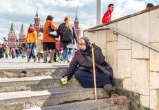 Femme agée s'asseyant sur des escaliers priant l'aumône photographie stock libre de droits
