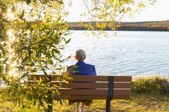 Femme agée s'asseyant sur un banc de parc Photos stock
