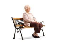 Femme agée s'asseyant sur un banc et regardant loin Image stock