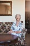 Femme agée s'asseyant sur un divan à la maison de vieillesse Photographie stock libre de droits