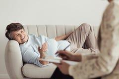 Femme agée satisfaisante sur le canapé Image stock