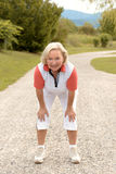 Femme agée sportive établissant sur une route rurale Photographie stock