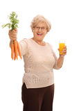 Femme agée tenant les carottes et le jus Photos stock
