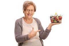 Femme agée tenant un petits panier à provisions et pointage Photo stock
