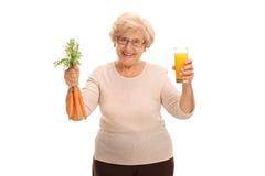 Femme agée tenant un verre de jus et de carottes Photo stock