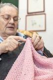 Femme agée tricotant la laine rose Image stock