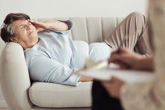 Femme agée triste avec le mal de tête Images stock
