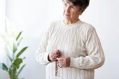 Femme agée triste et seule tenant le chapelet rouge avec la croix image stock