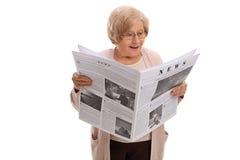 Femme agée étonnée lisant un journal Image libre de droits