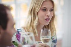 Femme agissant l'un sur l'autre tout en ayant le vin pendant le déjeuner Image stock