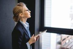 Femme agréable avec les cheveux justes tenant son ordinateur portable et regardant la fenêtre photographie stock