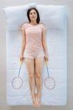 Femme agréable belle dormant avec des raquettes de badminton photo stock