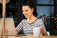 Femme agréable gaie mettant une tasse sur la table Photographie stock