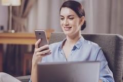 Femme agréable regardant l'écran de smartphone images stock