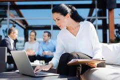 Femme agréable sérieuse regardant l'écran d'ordinateur portable Photographie stock
