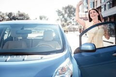 Femme agréable satisfaisante se tenant près de la voiture tenant la main  Photos stock