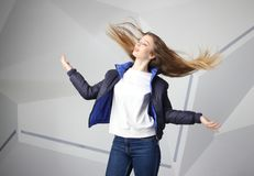 Femme agressive furieuse criarde de brune avec de longs poils de vol, portrait instantané de studio sur le mur moderne photographie stock libre de droits