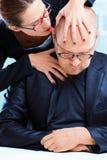 Femme agressive tourmentant l'homme sur le lieu de travail Photographie stock libre de droits