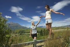 Femme aidant l'ami à marcher sur la barrière Image stock