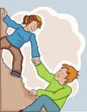 Femme aidant l'homme à escalader une falaise pointue. Photographie stock