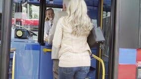 Femme aidant l'homme supérieur à monter à bord de l'autobus banque de vidéos