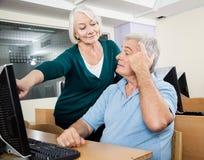 Femme aidant le camarade de classe masculin dans la classe d'ordinateur Images stock