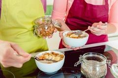 Femme ajoutant des écrimages au petit déjeuner de farine d'avoine photos libres de droits