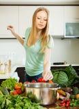 Femme ajoutant l'épice au pot Image stock